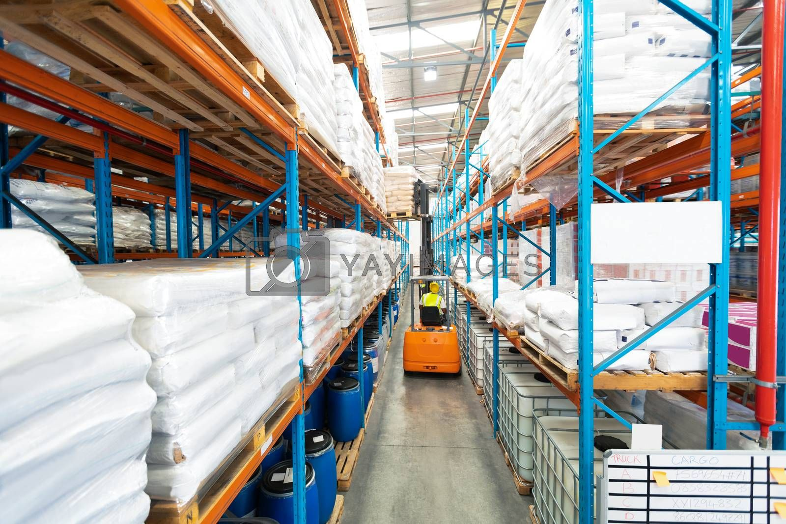 Rear view of mature African-american male worker driving forklift in warehouse. This is a freight transportation and distribution warehouse. Industrial and industrial workers concept