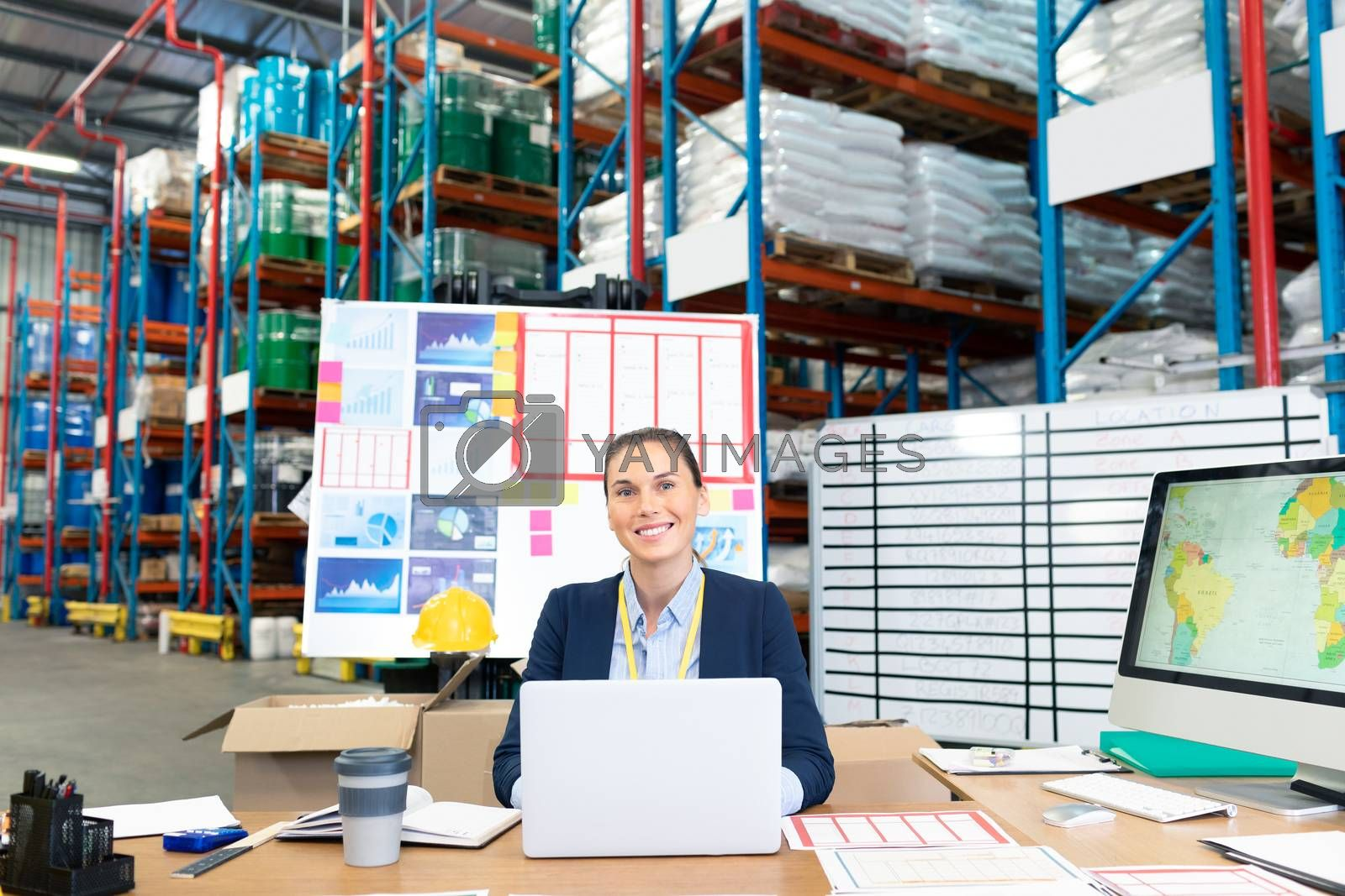 Royalty free image of Female manager using laptop at desk in warehouse by Wavebreakmedia