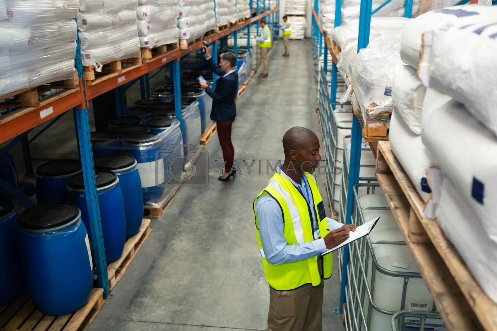 High angle side view of diverse warehouse staff checking stocks in aisle in warehouse. They are holding clipboards and writing in it. This is a freight transportation and distribution warehouse. Industrial and industrial workers concept