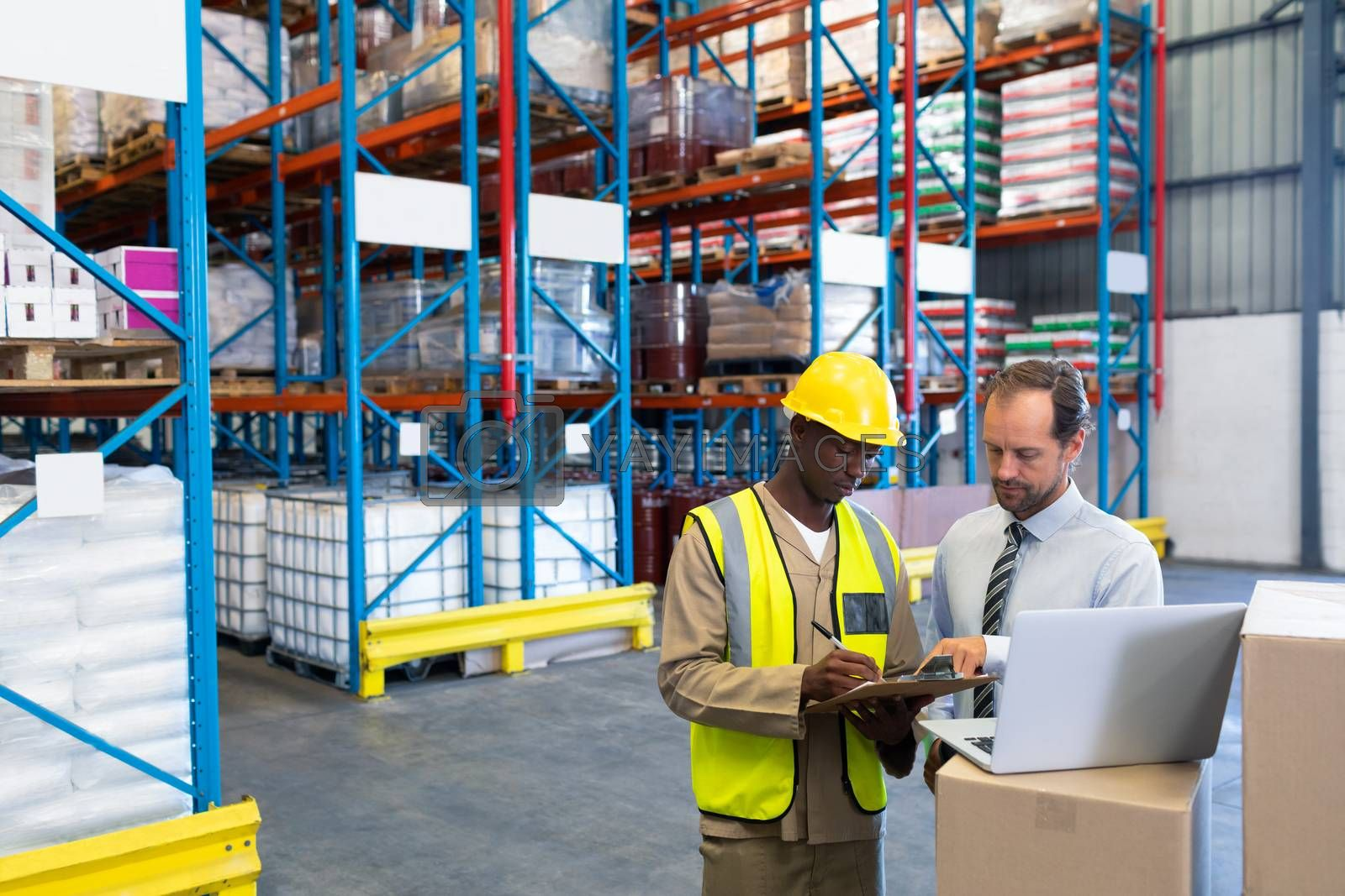 Front view of diverse staffs discussing over clipboard in warehouse. This is a freight transportation and distribution warehouse. Industrial and industrial workers concept