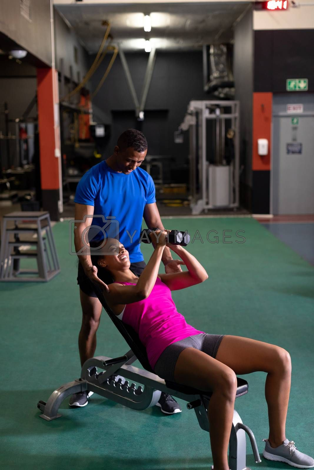 Side view of an African-American woman holding dumbbells while lying on an exercise bench and an African-American man assisting her inside a room at a sports centre. Bright modern gym with fit healthy people working out and training. Bright modern gym with fit healthy people working out and training