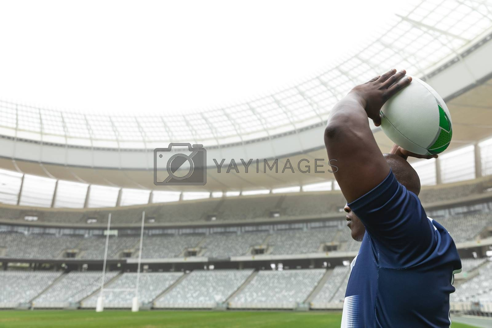 Side view of African American male rugby player throwing rugby ball in stadium