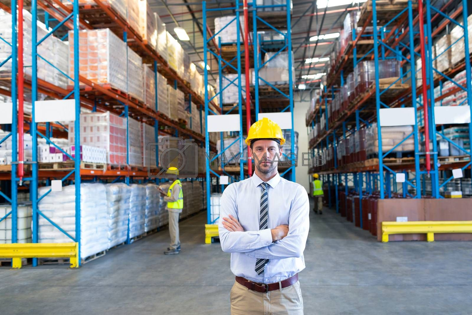 Front view of male supervisor standing with arms crossed and looking at camera in warehouse. This is a freight transportation and distribution warehouse. Industrial and industrial workers concept