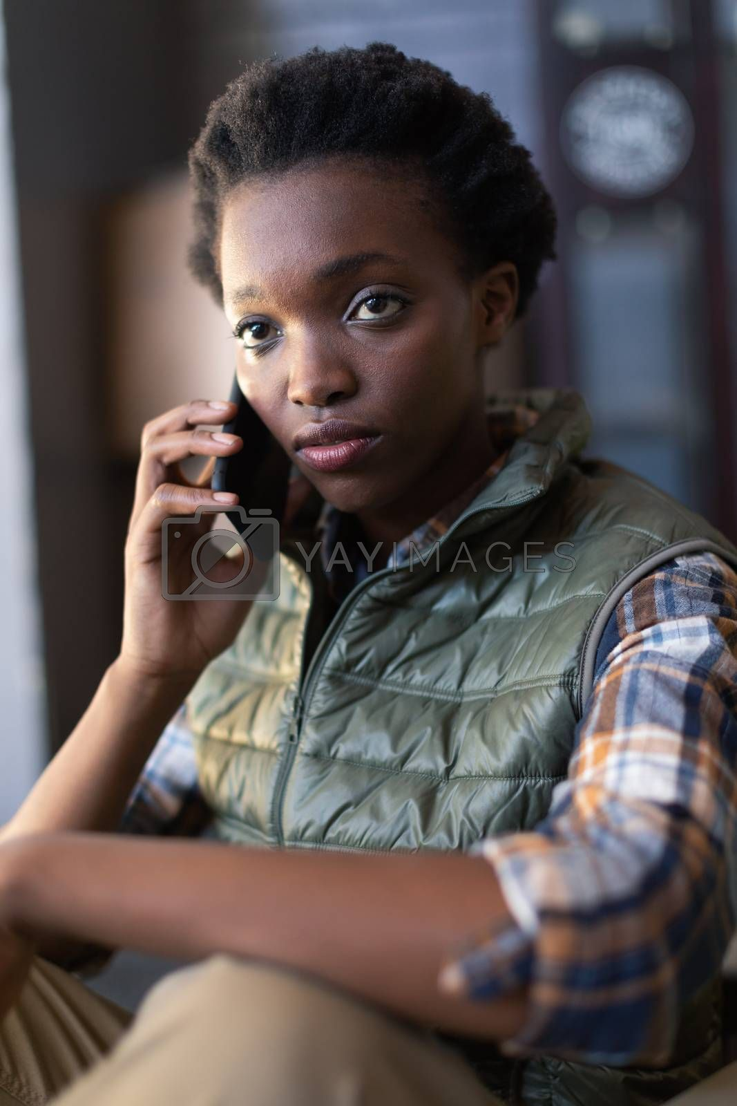Close-up of African-american female worker talking on mobile phone in warehouse. This is a freight transportation and distribution warehouse. Industrial and industrial workers concept