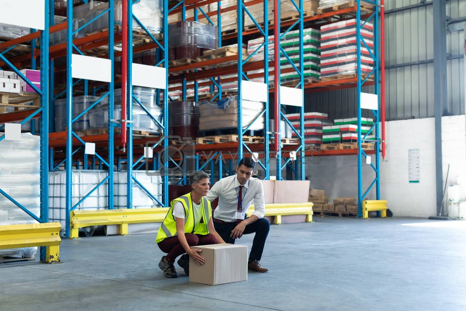 Large angle view of mixed-race Young male staff giving training to Caucasian female staff in warehouse. This is a freight transportation and distribution warehouse. Industrial and industrial workers concept