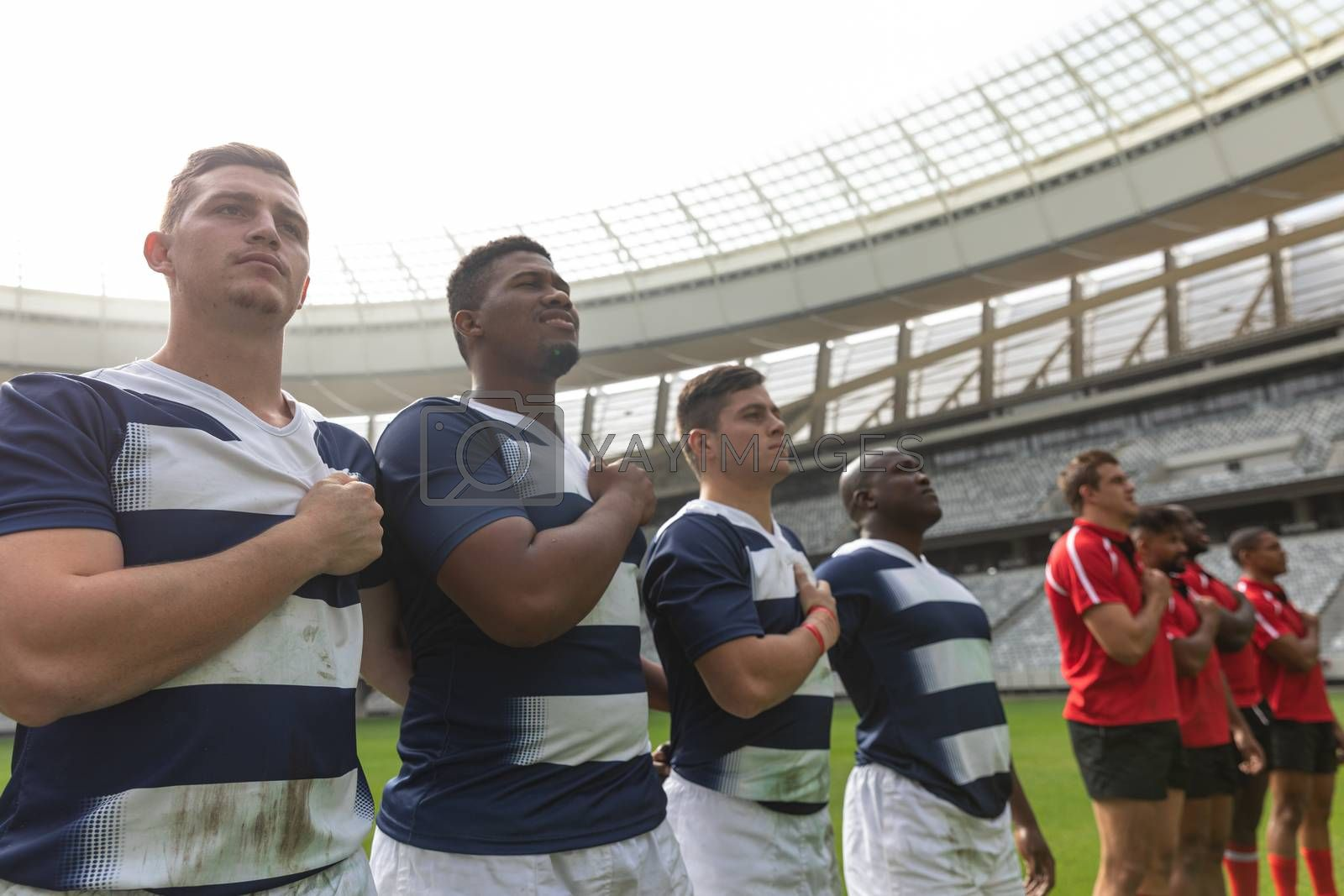 Front view of proud diverse male rugby team taking pledge together in stadium