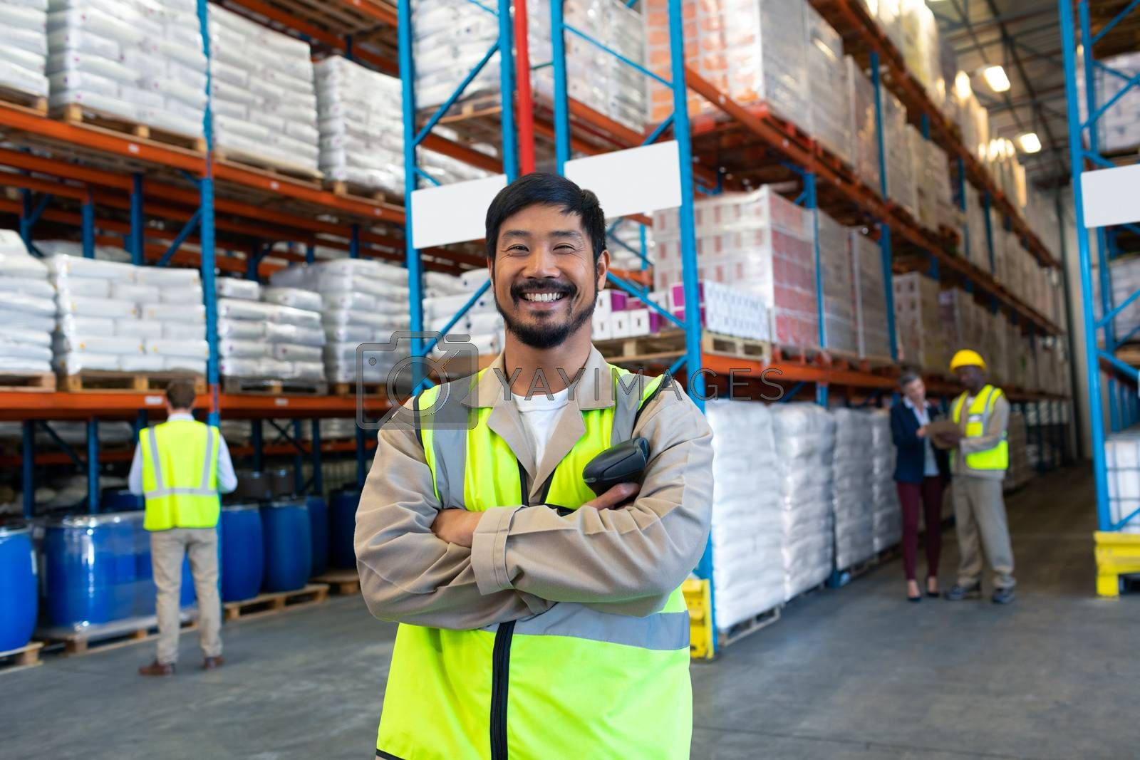 Front view of handsome Asian male worker standing with arms crossed and looking at camera in warehouse. Diverse colleagues working in the background. This is a freight transportation and distribution warehouse. Industrial and industrial workers concept