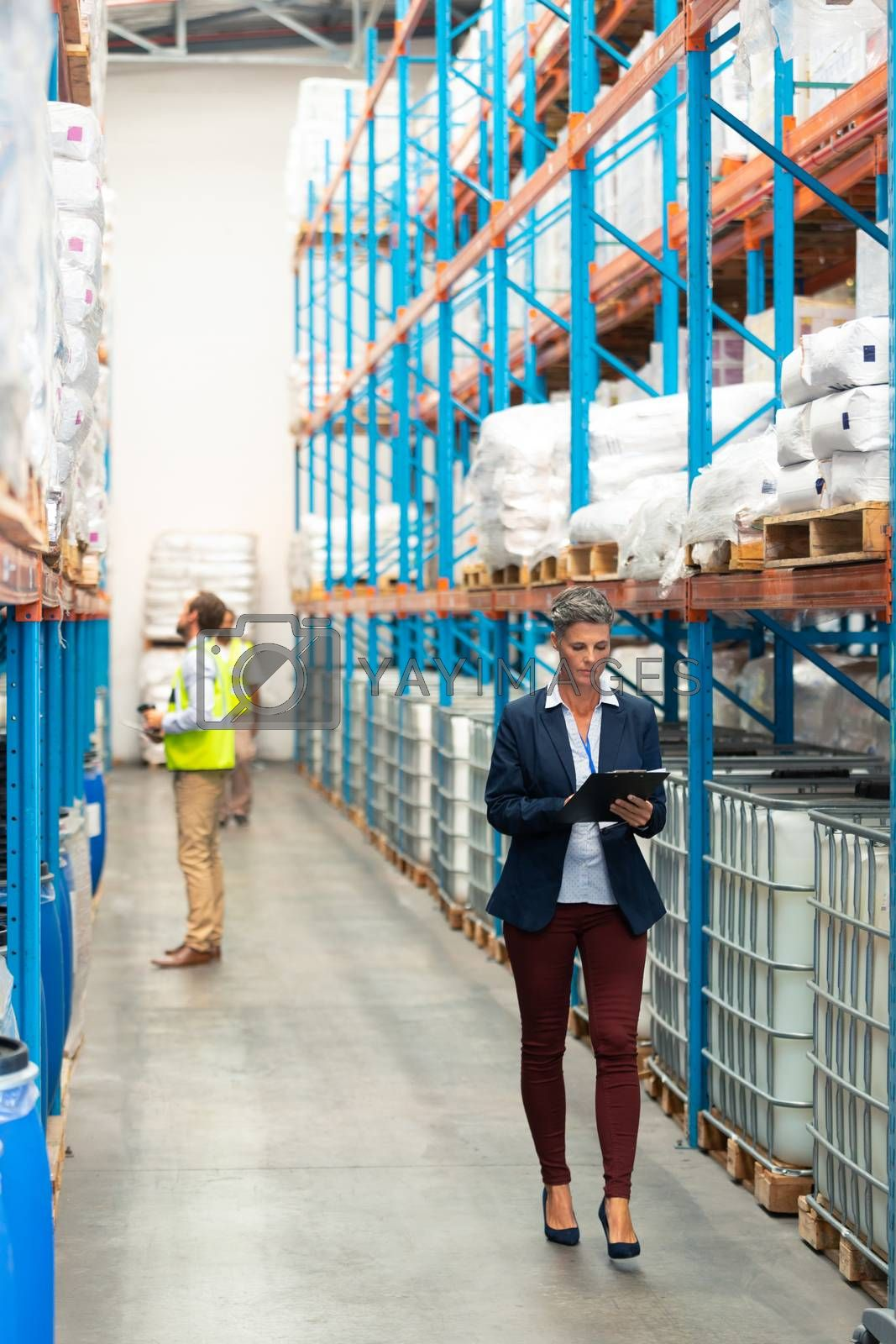 Front view of pretty Caucasian female manager working on clipboard while walking in warehouse. Diverse male staff work behind her. This is a freight transportation and distribution warehouse. Industrial and industrial workers concept