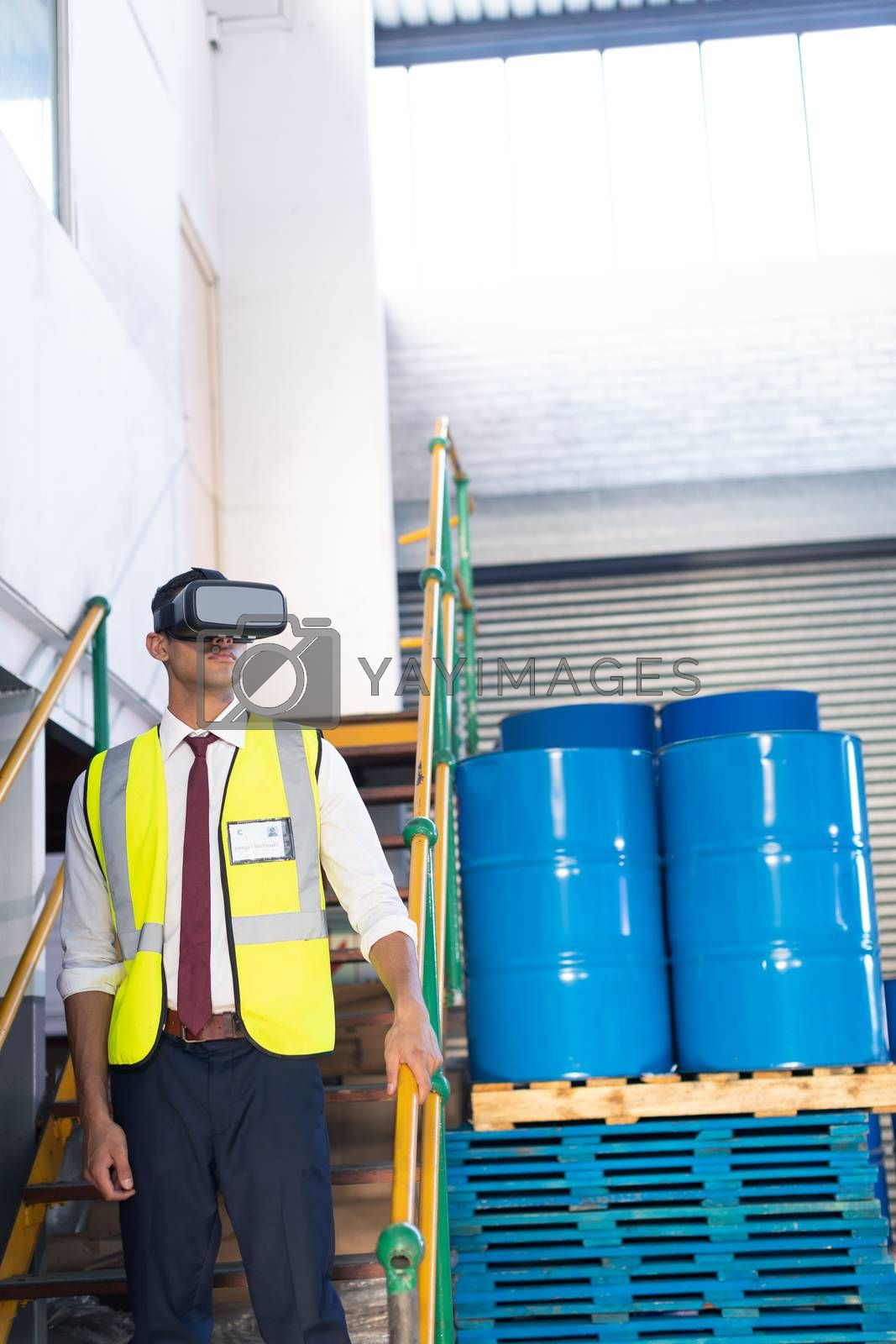 Front view of young Caucasian male supervisor using virtual reality headset in warehouse. This is a freight transportation and distribution warehouse. Industrial and industrial workers concept
