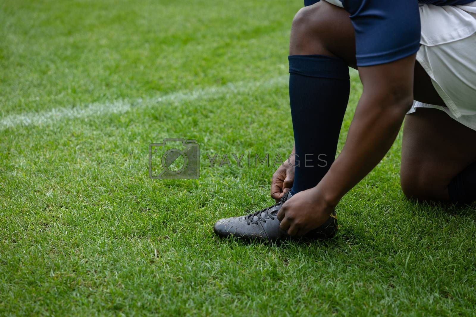 Low section of  African american male rugby player tying shoelaces in the stadium