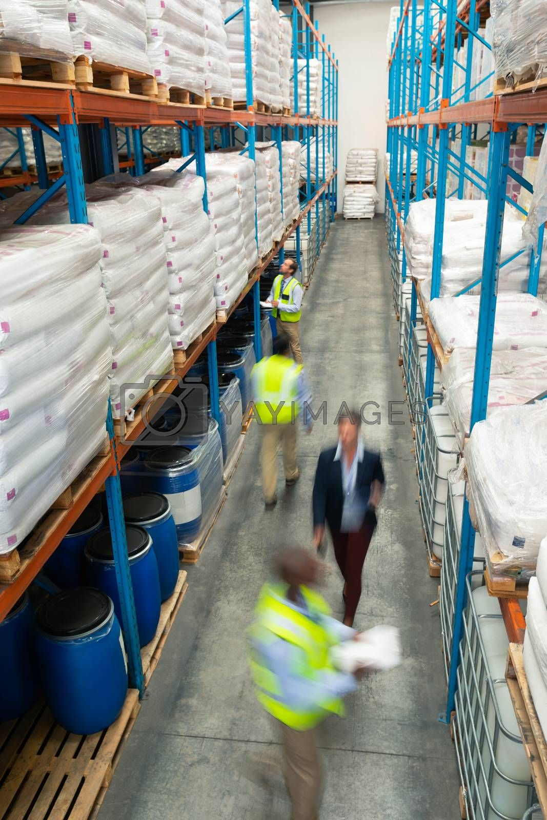 High angle view of diverse warehouse staff checking stocks in aisle in warehouse. They are holding clipboards and walking in aisle. This is a freight transportation and distribution warehouse. Industrial and industrial workers concept