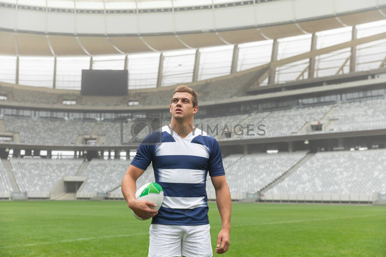 Front view of thoughtful Caucasian rugby player standing with rugby ball in stadium
