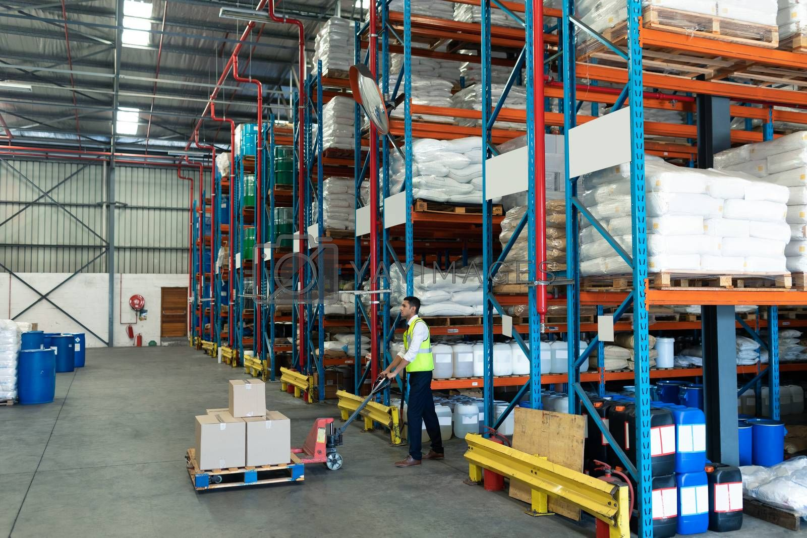 Side view of Young Caucasian male staff using pallet jack in warehouse. This is a freight transportation and distribution warehouse. Industrial and industrial workers concept