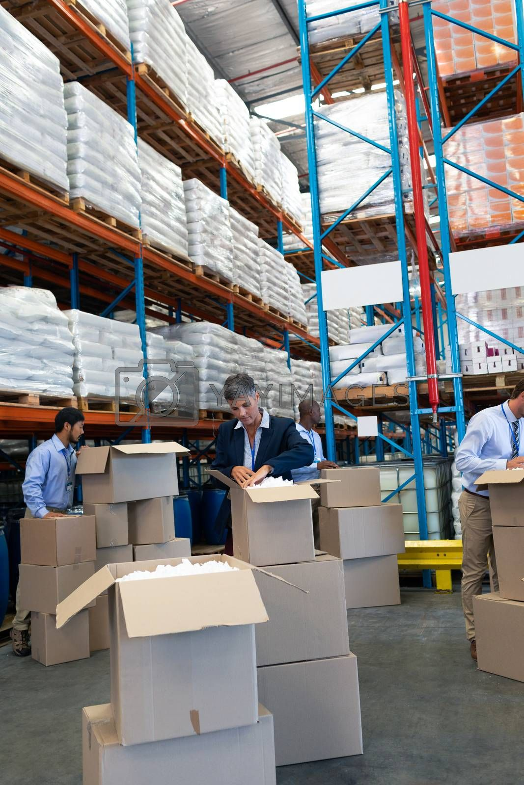 Front view of mature diverse staff unpacking cardboard boxes in warehouse. This is a freight transportation and distribution warehouse. Industrial and industrial workers concept