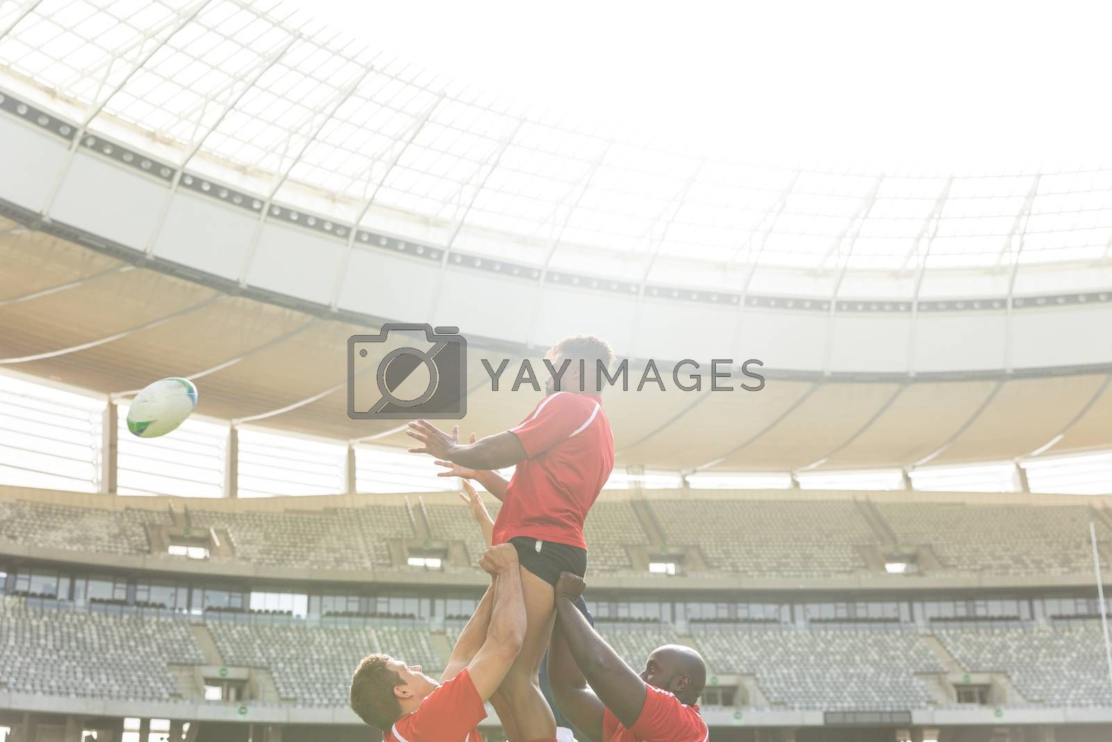 Low angle side view of African American male rugby player trying to catch the ball while diverse rugby players hold him in the air in stadium on sunny day.