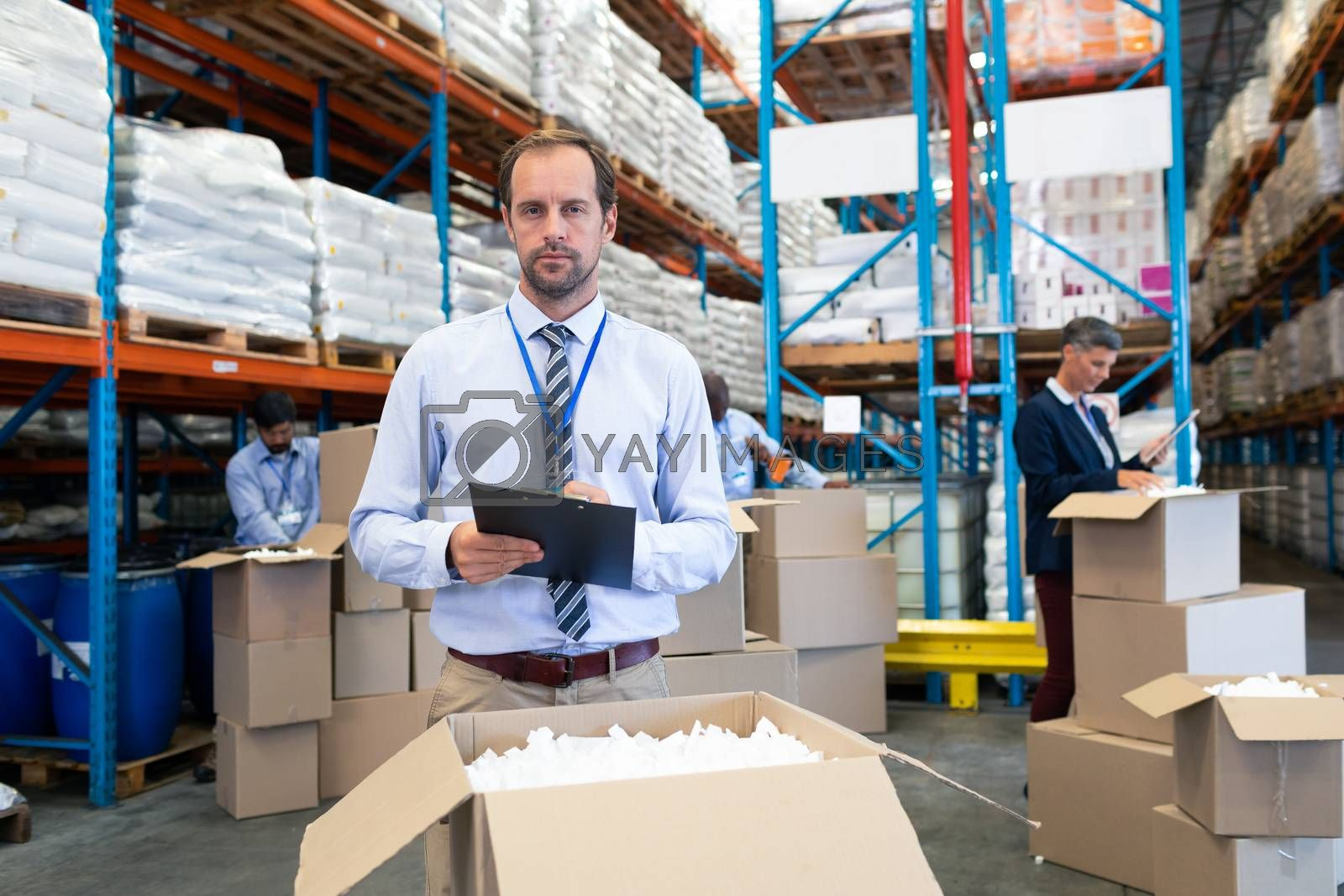 Front view of handsome Caucasian male supervisor checking stocks and looking at camera in warehouse. Diverse warehouse workers unpacking cardboard boxes. This is a freight transportation and distribution warehouse. Industrial and industrial workers concept