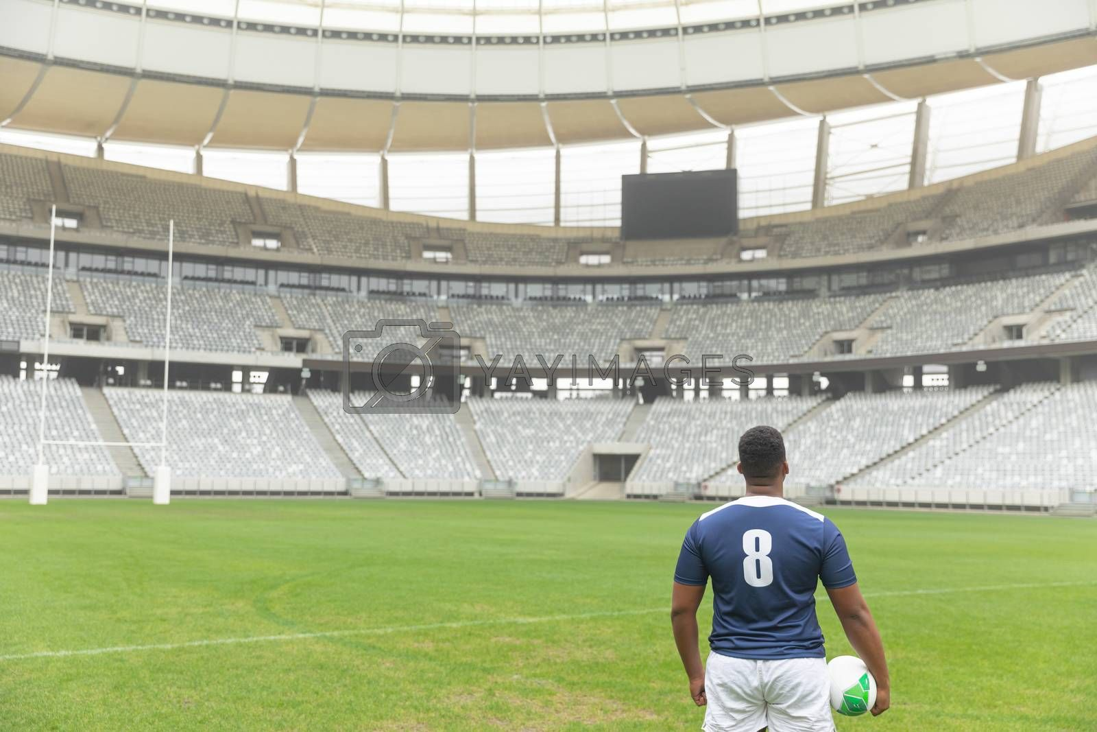 Rear view of African American rugby player standing with rugby ball in the stadium