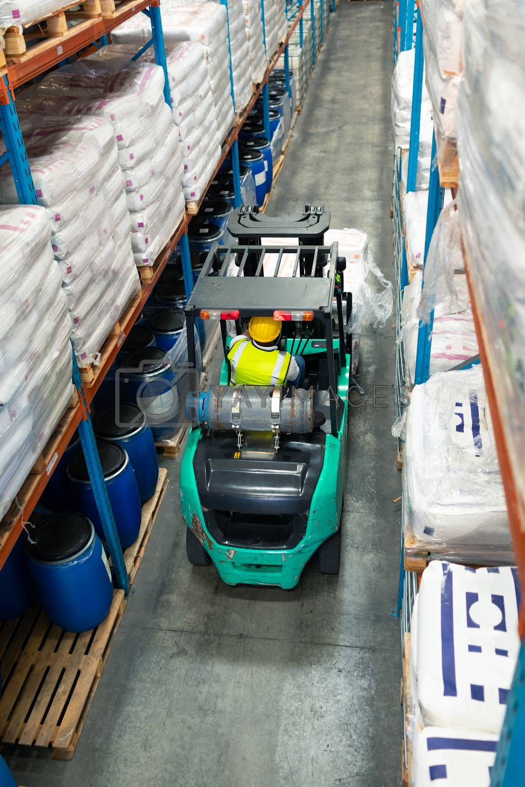 High angle rear view of African-american male worker driving forklift in warehouse. This is a freight transportation and distribution warehouse. Industrial and industrial workers concept