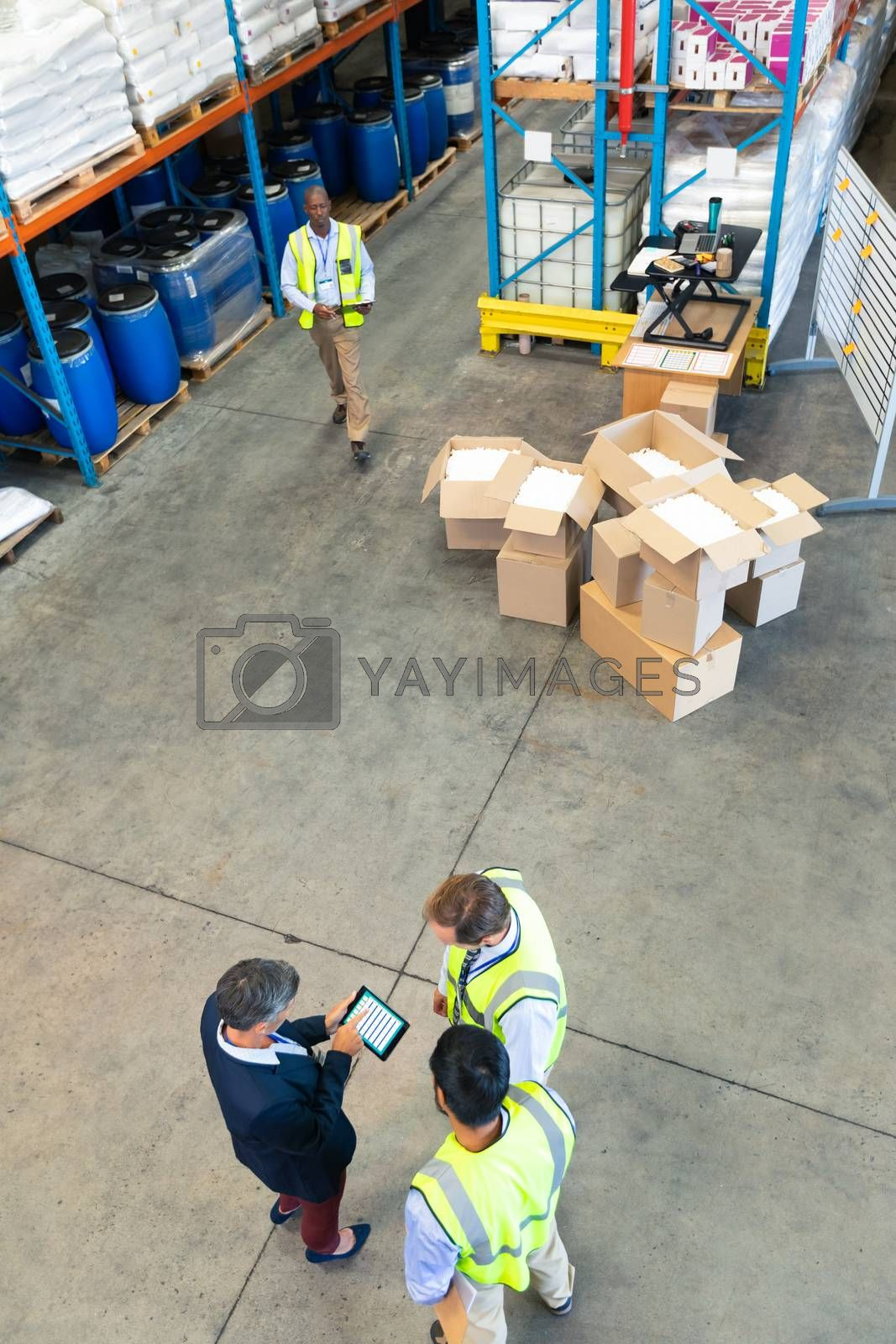 High angle view of diverse mature warehouse staff discussing over digital tablet in warehouse. This is a freight transportation and distribution warehouse. Industrial and industrial workers concept