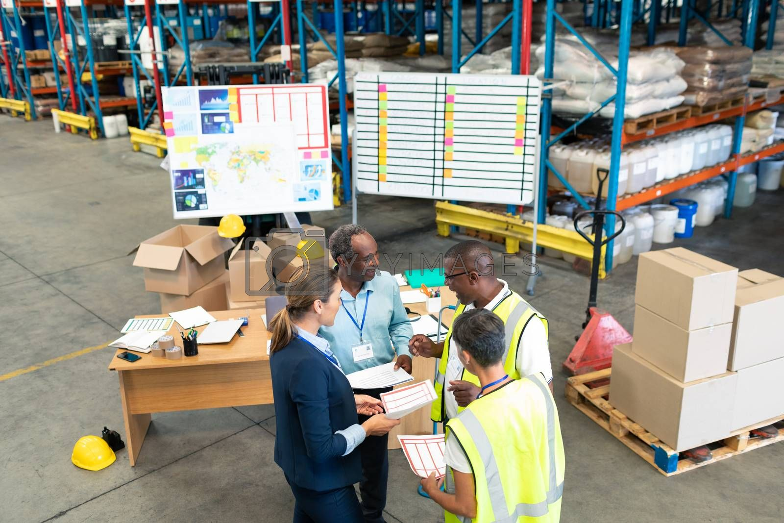 High angle view of mature diverse staffs discussing over document in warehouse. This is a freight transportation and distribution warehouse. Industrial and industrial workers concept