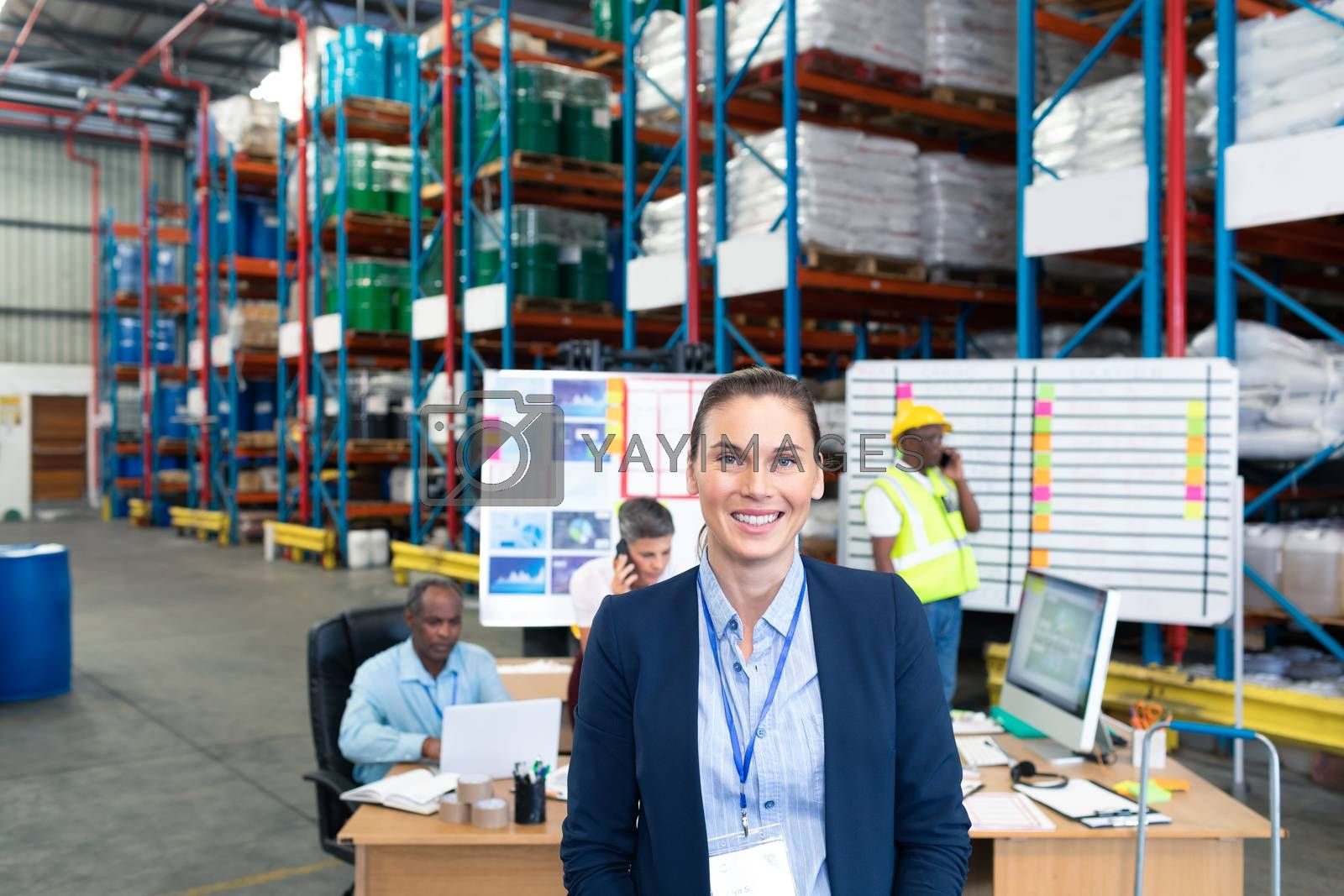 Portrait of happy mature Caucasian female manager looking at camera in warehouse. Diverse colleagues are working in the background. This is a freight transportation and distribution warehouse. Industrial and industrial workers concept