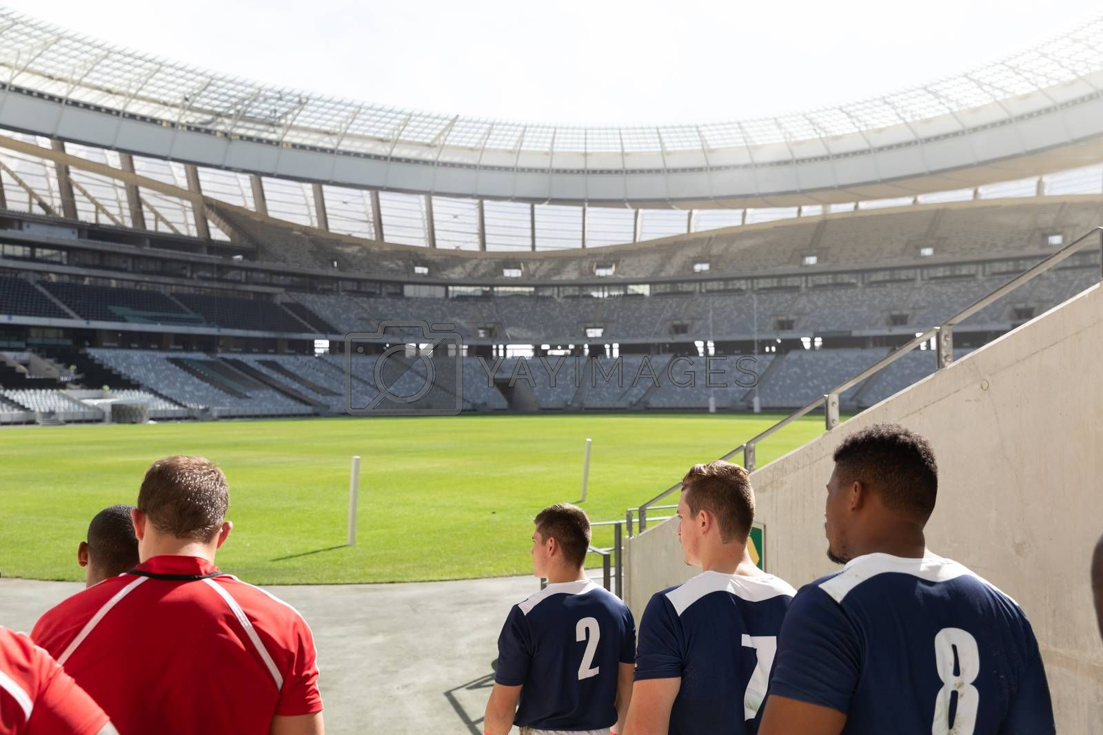 Rear view of active diverse male rugby players standing in a row at stadium for match on a sunny day.