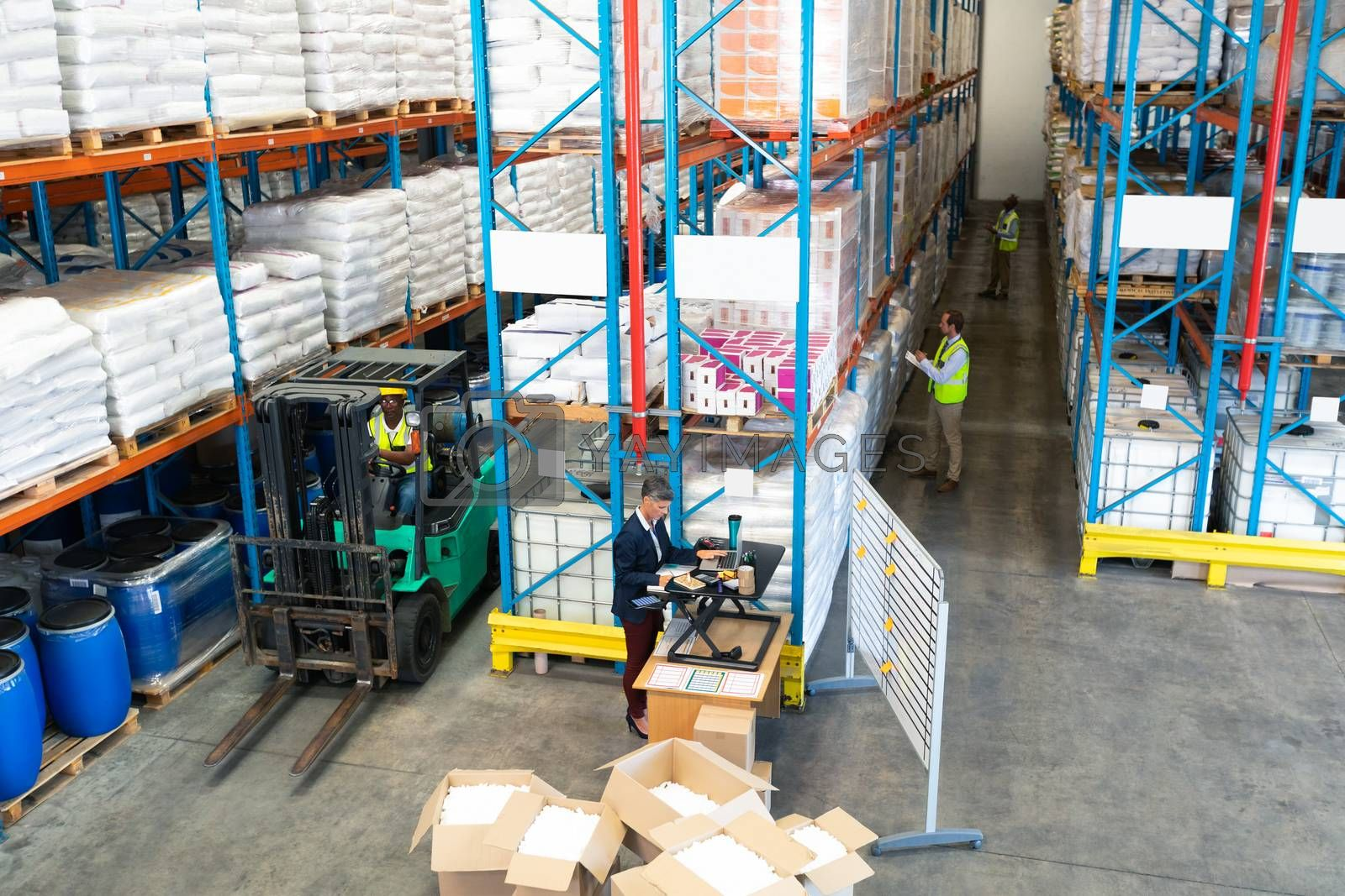 High angle view of mature diverse warehouse staff working together in warehouse. African-american worker driving a forklift in warehouse. This is a freight transportation and distribution warehouse. Industrial and industrial workers concept