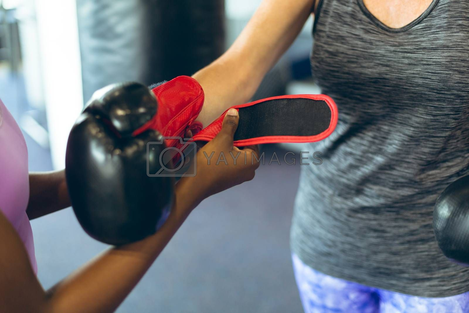 Close-up of young African-american female trainer helping Senior Caucasian female athletic to wear boxing gloves in fitness center. Bright modern gym with fit healthy people working out and training