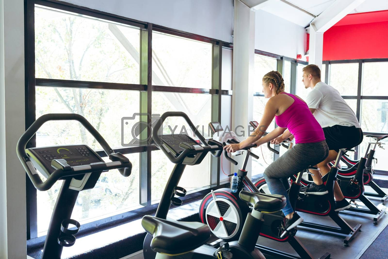 Rear view of young Caucasian male and female athlete exercising with exercise bike in fitness center. Bright modern gym with fit healthy people working out and training
