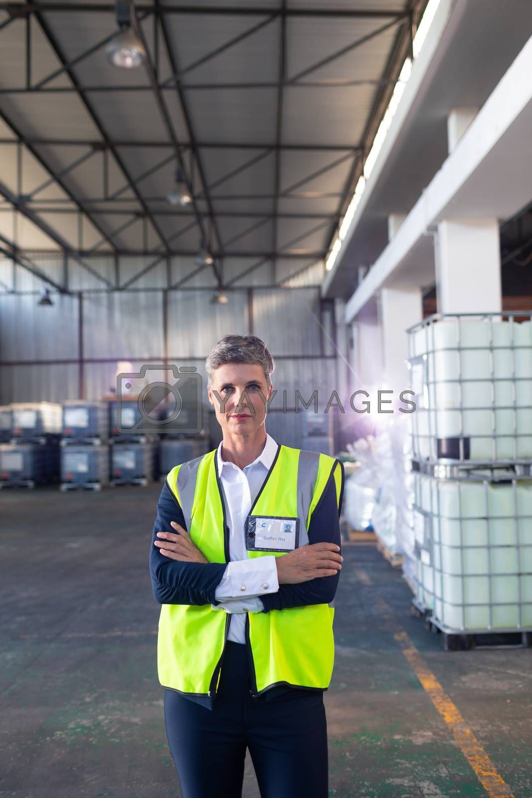 Portrait of Caucasian mature female staff in reflective jacket standing with arms crossed in warehouse. This is a freight transportation and distribution warehouse. Industrial and industrial workers concept