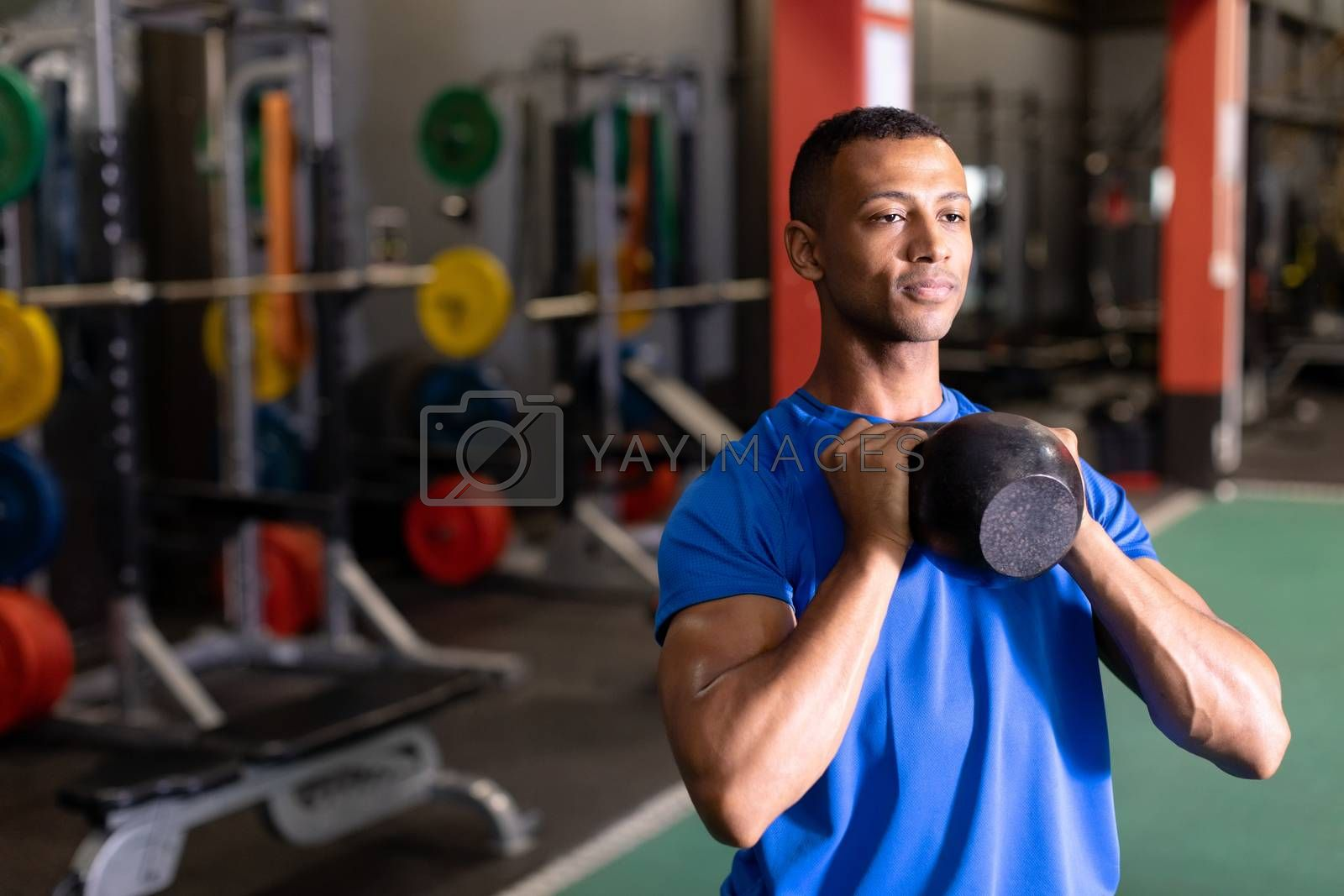 Front view of an African-American man lifting ball weights with both arms inside a room at a sports centre. Bright modern gym with fit healthy people working out and training. Bright modern gym with fit healthy people working out and training
