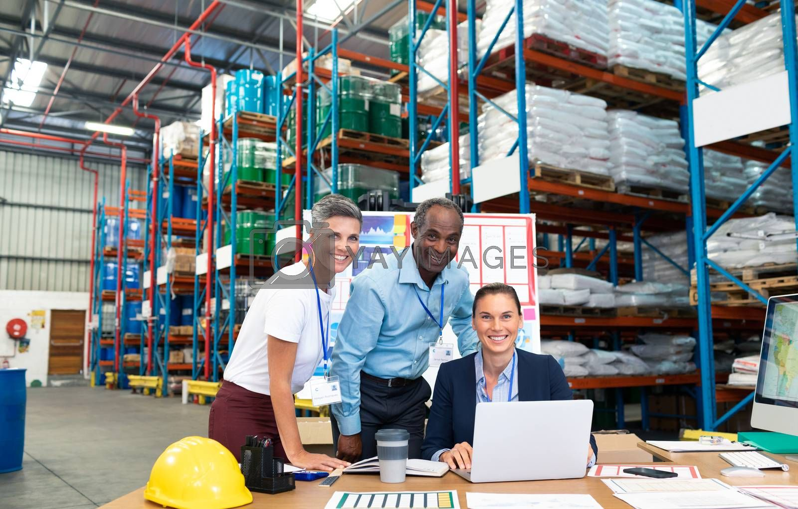 Portrait of beautiful Caucasian female manager with her coworkers discussing over laptop at desk in warehouse. This is a freight transportation and distribution warehouse. Industrial and industrial workers concept
