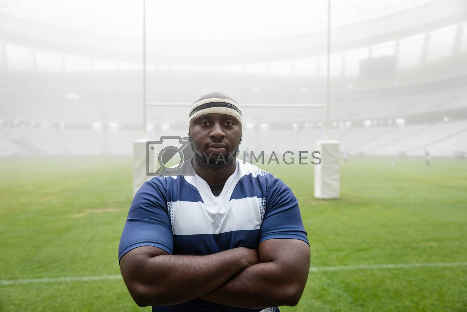 Portrait of African american male rugby player standing with arms crossed in stadium