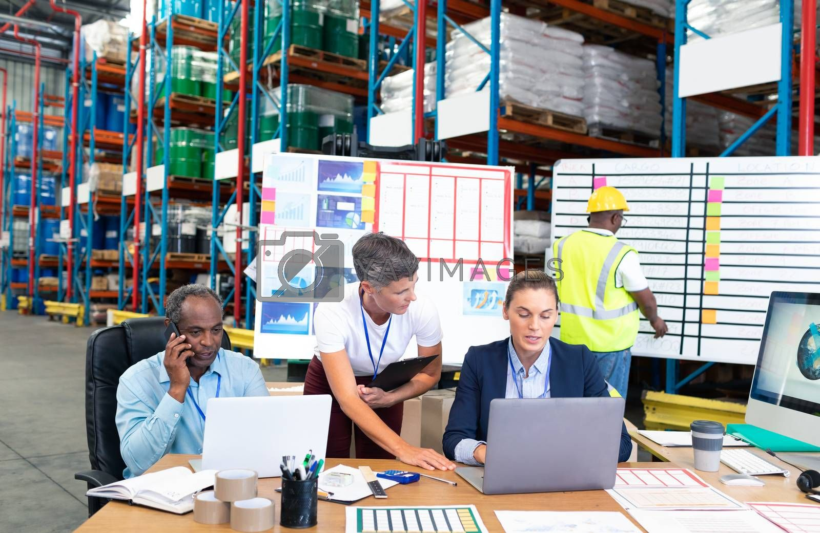 Front view of mature Caucasian female manager with her coworker discussing over laptop at desk in warehouse. This is a freight transportation and distribution warehouse. Industrial and industrial workers concept