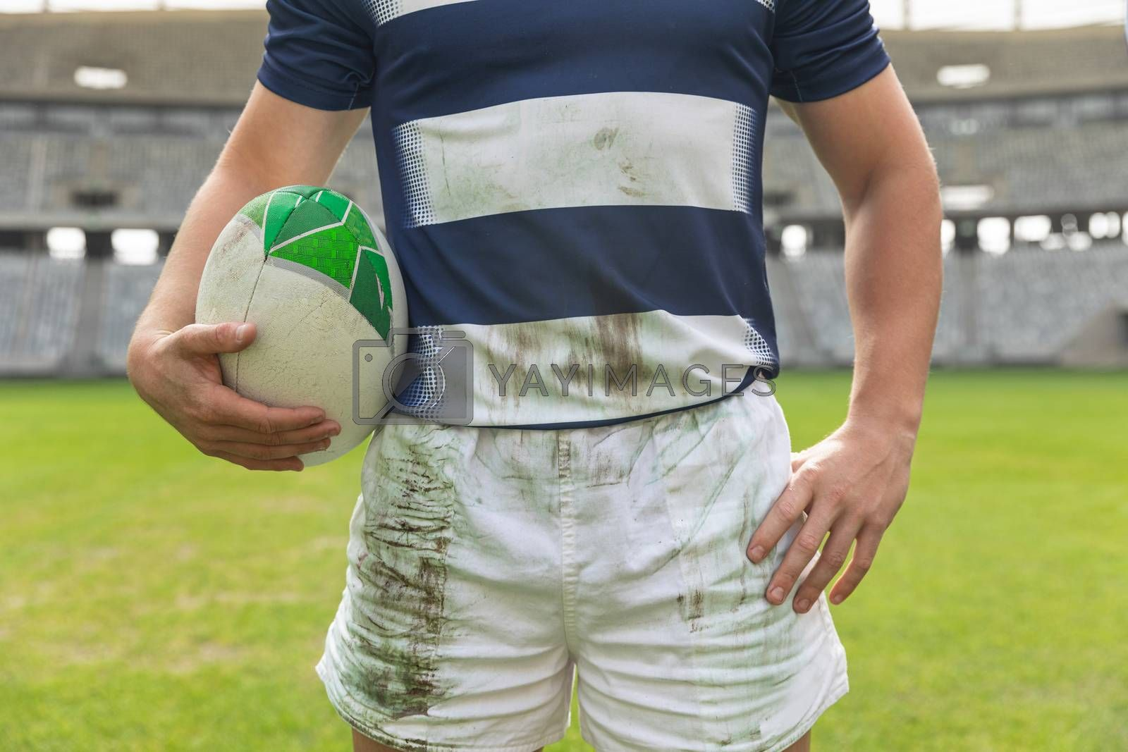Mid section close up of Caucasian male rugby player standing with rugby ball in stadium
