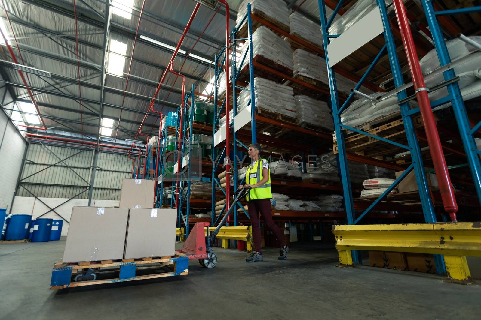 Low angle of Mature Caucasian female staff using pallet jack in warehouse. This is a freight transportation and distribution warehouse. Industrial and industrial workers concept