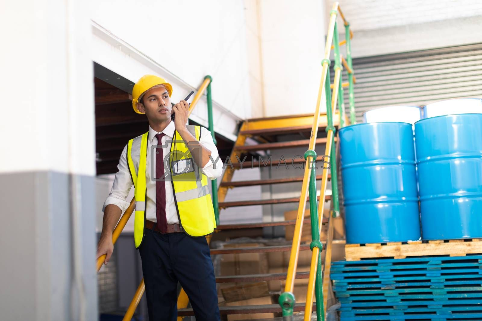 Front view of Caucasian male supervisor talking on talkie walkie on stairs in warehouse. This is a freight transportation and distribution warehouse. Industrial and industrial workers concept