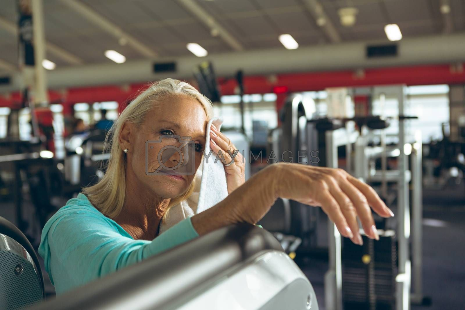 Front view of tired active senior Caucasian woman wiping sweat towel in fitness studio. Strong active senior female amputee training and working out