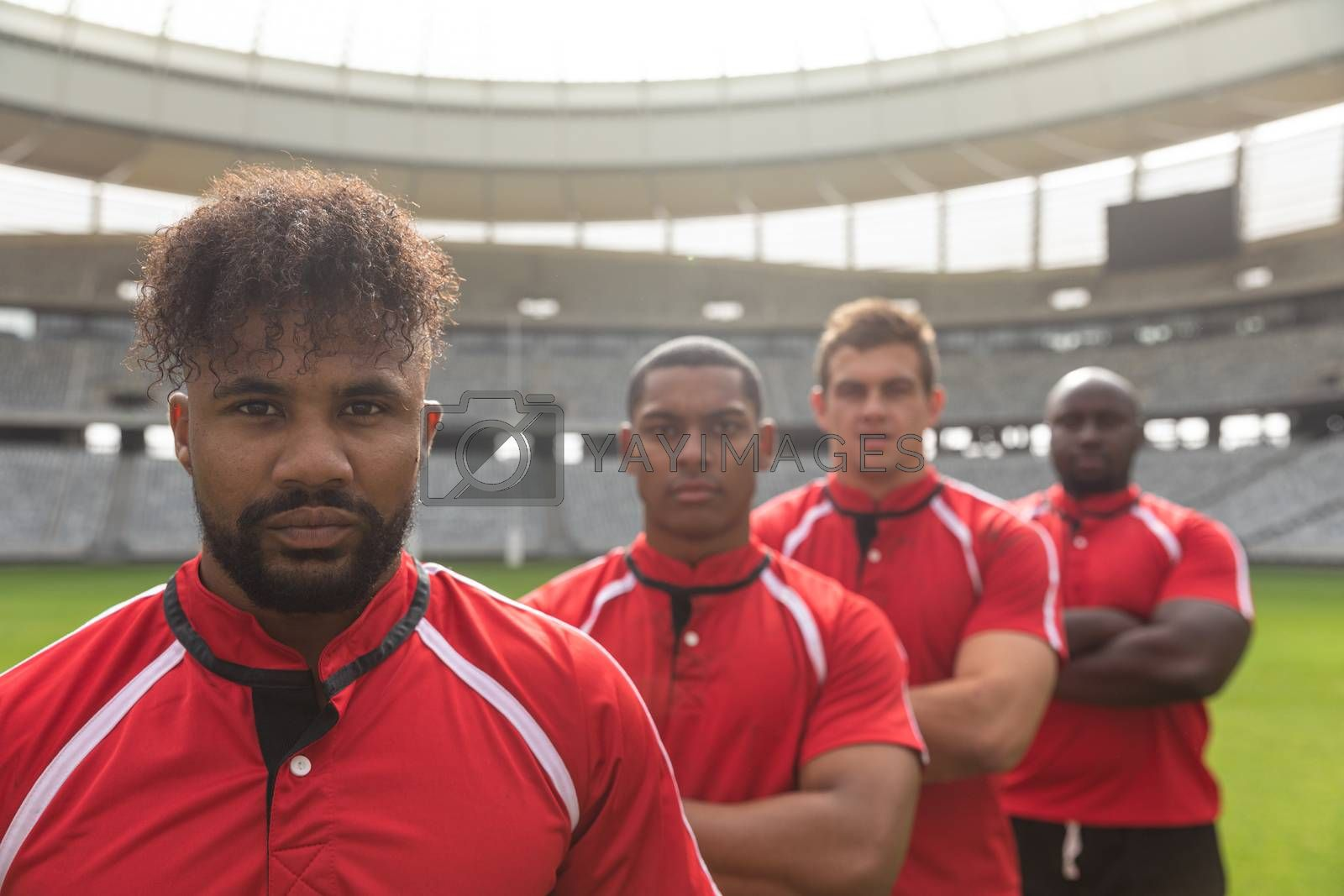 Portrait of diverse male rugby players standing together with arms crossed in stadium on sunny day.
