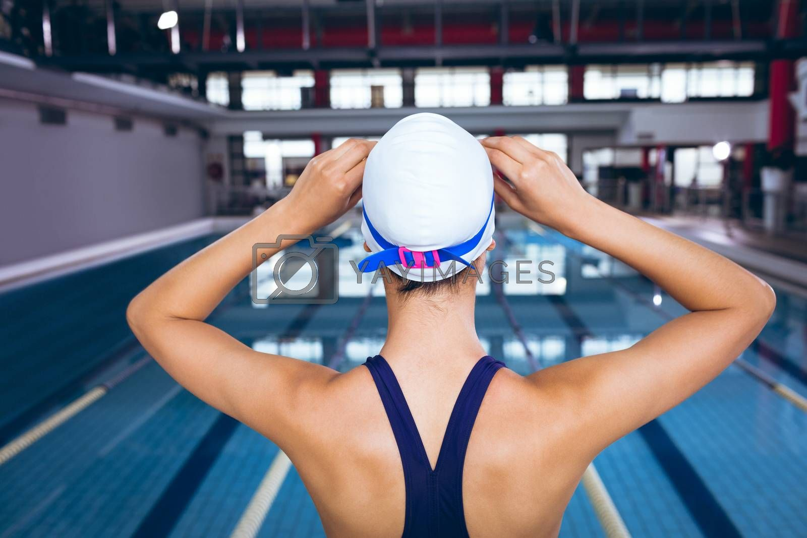 Rear view of a young African-American woman wearing a swimsuit and swimming cap with goggles while standing by an olympic sized pool inside a stadium. Bright modern gym with fit healthy people working out and training