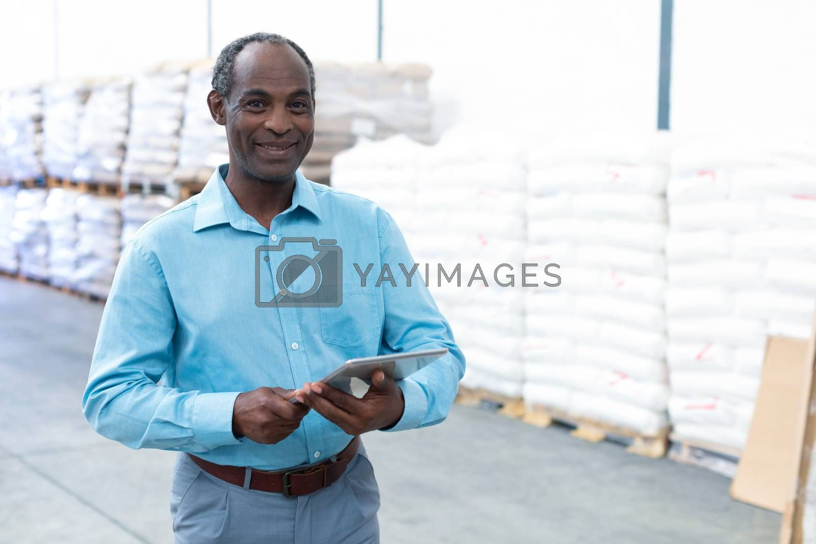 Portrait of happy handsome mature African-american male supervisor looking at camera while working on digital tablet in warehouse. This is a freight transportation and distribution warehouse. Industrial and industrial workers concept