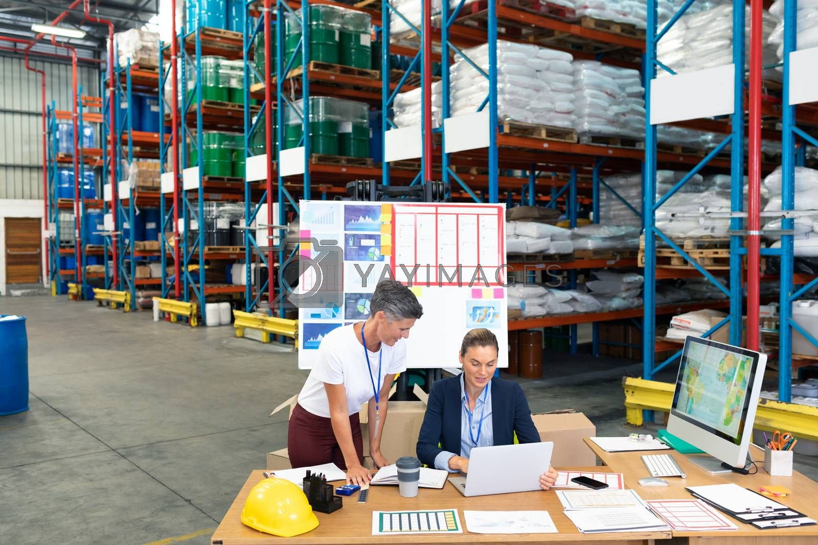 High angle view of beautiful Caucasian female manager with her coworker discussing over laptop at desk in warehouse. This is a freight transportation and distribution warehouse. Industrial and industrial workers concept