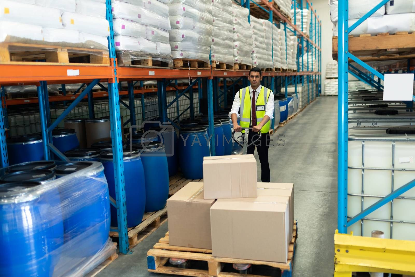 Front view of Caucasian male staff using pallet jack in warehouse. This is a freight transportation and distribution warehouse. Industrial and industrial workers concept