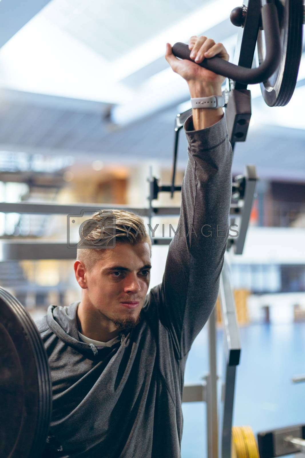 Close-up of handsome young Caucasian man exercising with shoulder machine in fitness studio. Bright modern gym with fit healthy people working out and training