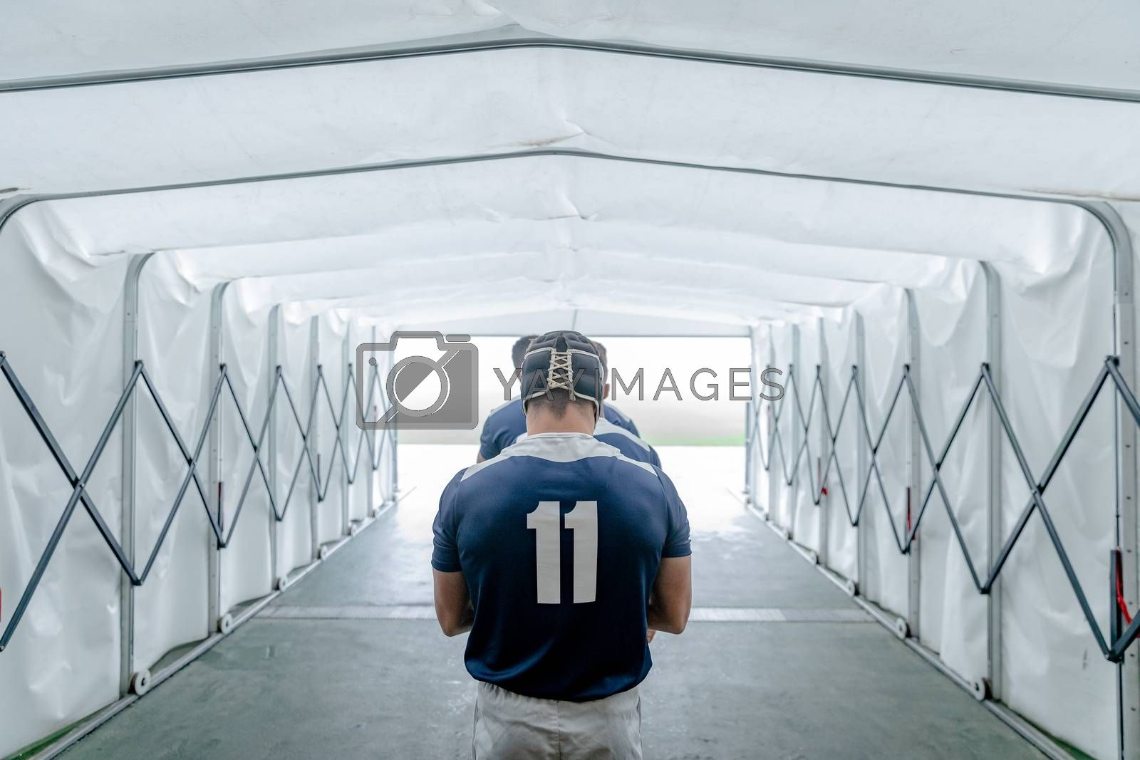Rear view of diverse male rugby players standing together in a row at the entrance of stadium