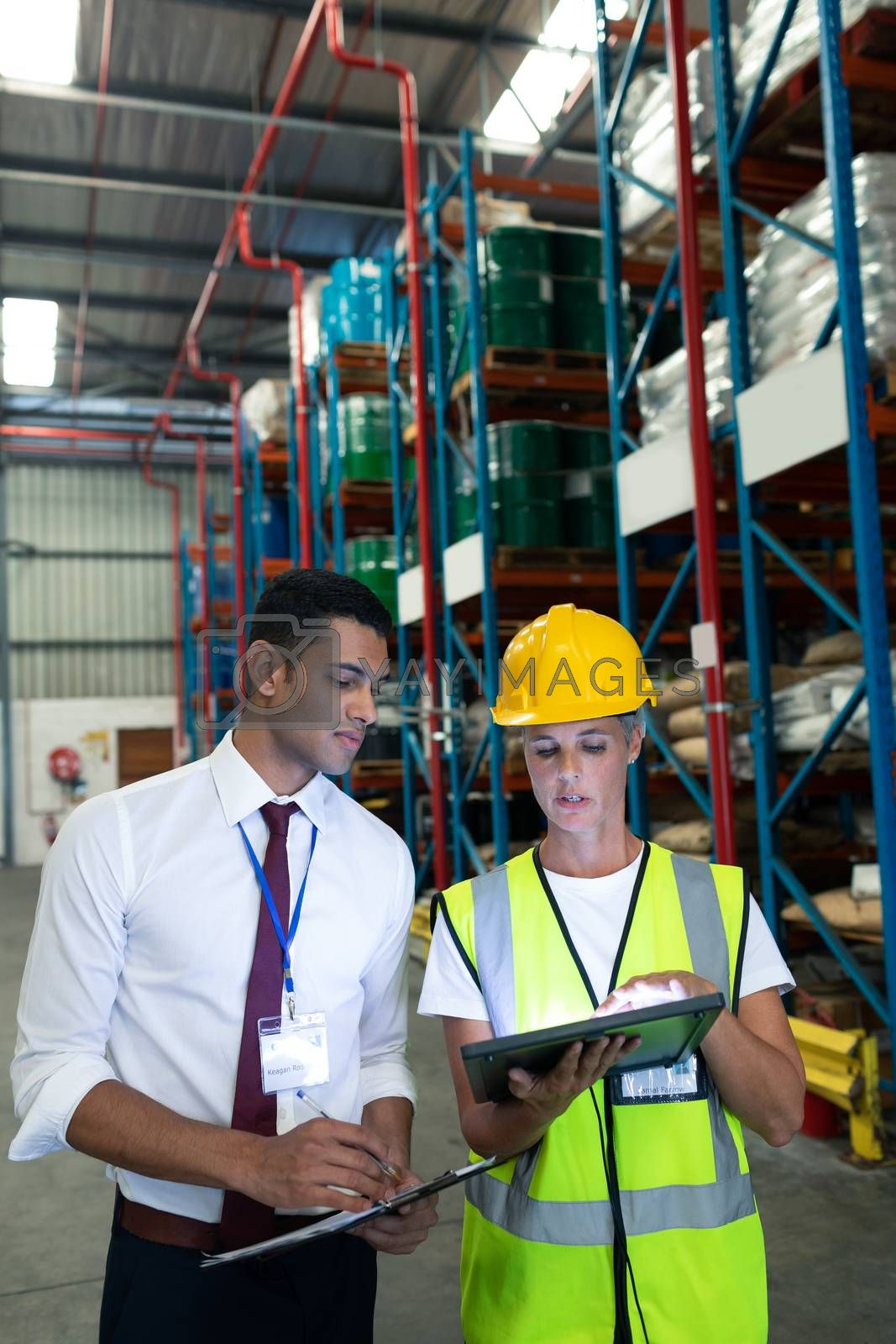 Front view of diverse Attentive warehouse staffs discussing over digital tablet in warehouse. This is a freight transportation and distribution warehouse. Industrial and industrial workers concept