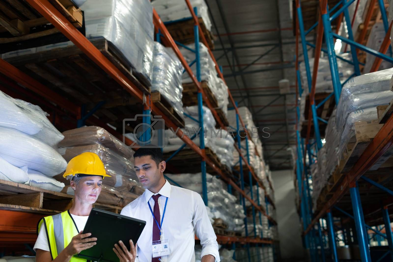 Front view of mixed-race Attentive male and female staffs discussing over digital tablet in warehouse. This is a freight transportation and distribution warehouse. Industrial and industrial workers concept