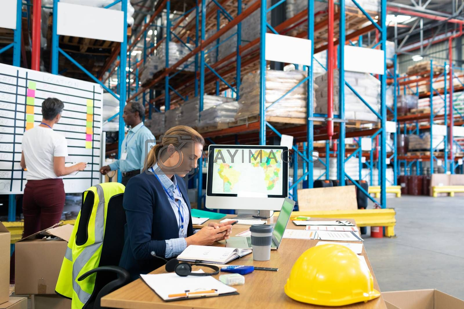 Side view of beautiful Caucasian female manager using mobile phone at desk in warehouse. In the background diverse colleagues are discussing in front of whiteboard. This is a freight transportation and distribution warehouse. Industrial and industrial workers concept