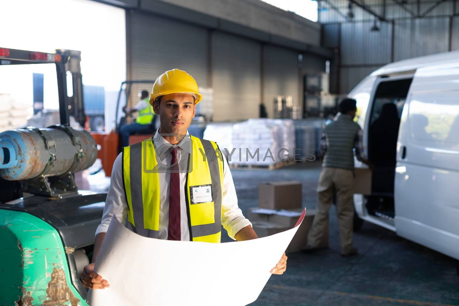 Portrait of young Caucasian male supervisor looking at blueprint in warehouse. This is a freight transportation and distribution warehouse. Industrial and industrial workers concept
