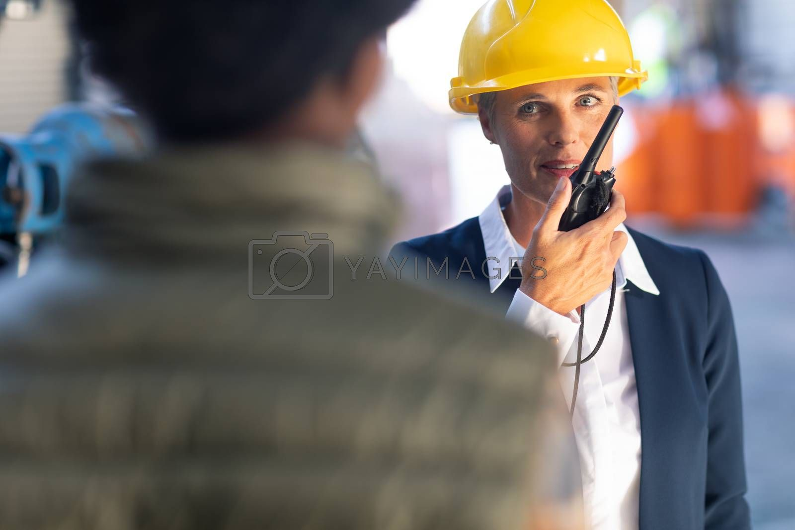 Front view of Caucasian Mature female manager talking on walkie talkie in warehouse. This is a freight transportation and distribution warehouse. Industrial and industrial workers concept